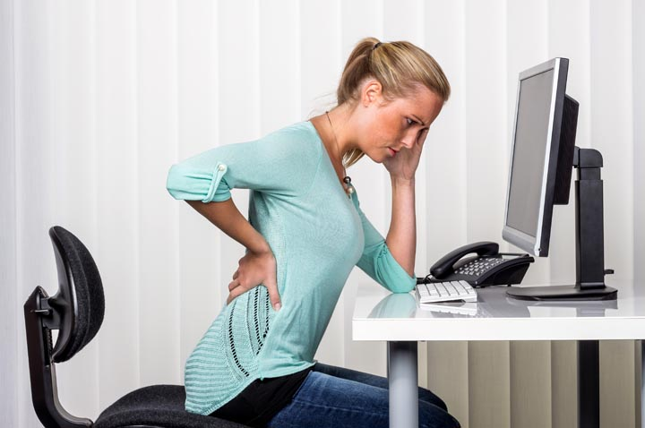 a woman sitting at a desk and has pain in the back